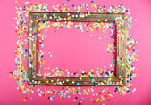 Photoframe with confetti on pink background — Stock Photo