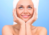 Beautiful young woman after shower with a towel on her head on blue background close-up — Stock Photo