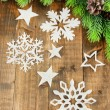 Beautiful paper snowflakes with fir branch on wooden background — Stock Photo #45233367