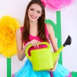 Beautiful young woman in petty skirt holding watering can on decorative background — Stock Photo