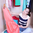 Beautiful young woman sitting on floor near wardrobe in room — Stock Photo #45239397