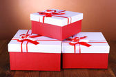 Beautiful gift boxes on table on brown background — Stock Photo