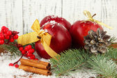 Christmas composition with red winter apples on wooden background — Stock Photo