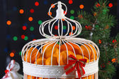 Tangerines in decorative cage with Christmas decor, on shiny background — Stok fotoğraf