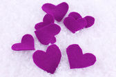 Little felt hearts on snowy background — Stock Photo