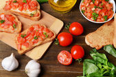 Delicious bruschetta with tomatoes on cutting board close-up — Stock Photo