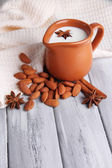 Almond milk in jug with almonds in bowl, on color wooden background — Stock Photo