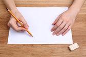 Ludzkie ręce ołówek pisać na papier i wymaż gumy na tle drewniany stół — Zdjęcie stockowe