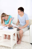 Young couple calculating finance at desk, on home interior background — Stock Photo