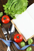 Cutlery tied with measuring tape and book with vegetables on wooden background — Photo
