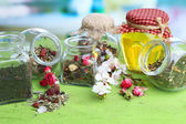 Assortment of herbs and tea and honey in glass jars on wooden table, on bright background  — Stockfoto