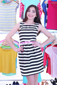 Beautiful young woman near rack with hangers — Zdjęcie stockowe