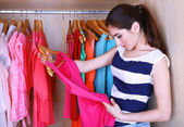 Young woman choose clothes in wardrobe at home — Stock Photo