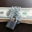 Dollars currency with lock and chain on wooden table — Stock Photo #45242019