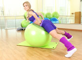 Young woman training with gymnastic ball in gym — ストック写真