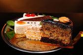 Assortment of pieces of cake, on dark background — Stockfoto