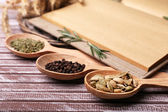 Different spices and cook book on wooden table, close up — Foto Stock