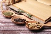 Especiarias diferentes e o livro do cozinheiro na mesa de madeira, close-up — Foto Stock