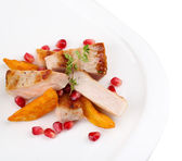 Grilled meat  with fried potato pieces and pomegranate seeds on plate, isolated on white — Stock Photo