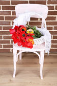 Bouquet of colorful tulips in wicker basket, on chair, on home interior background — Stockfoto