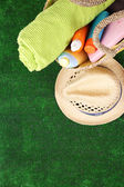 Wicker bag with colorful scarf, towel, bottles of lotions on  green background. — Stock Photo