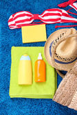 Wicker bag, swimsuit, bottles with lotions on color background. — Stock Photo