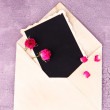 Old envelope with blank photo paper and beautiful pink dried roses on wooden background — Stock Photo #45268751