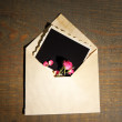 Old envelope with blank photo paper and beautiful pink dried roses on wooden background — Stock Photo #45268759
