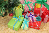 Many colorful presents with luxury ribbons  on color carpet background — Stok fotoğraf