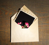 Old envelope with blank photo paper and beautiful pink dried roses on wooden background — Foto Stock