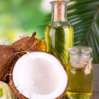 Coconuts and coconut oil on wooden table, on nature background — Stock Photo #45338277