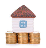 House standing on heap of coins isolated on white — Stock Photo