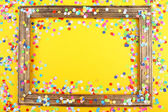Photoframe with confetti on yellow background — Stock Photo
