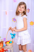 Beautiful small girl holding basket with colorful eggs on decorative background — Stock Photo