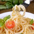 Delicious spaghetti with tomatoes on plate on table close-up — Stock Photo #45397923