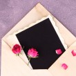Old envelope with blank photo paper and beautiful pink dried roses on wooden background — Stock Photo #45398839
