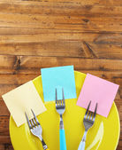 Empty note papers attached to forks, on plate, on color wooden background  — Стоковое фото