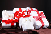 Beautiful gifts with red ribbons on silk, on dark background — Stock Photo