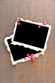 Blank photo paper and beautiful pink dried roses on wooden background — Zdjęcie stockowe