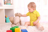 Cute little boy with wooden toy blocks in room — Stock Photo