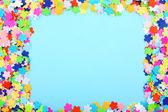 Confetti frame on blue background — Stock Photo