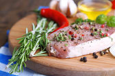 Raw meat steak with herbs and spices on cutting board, on wooden background — Stock Photo