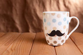 Cup with mustache on table on brown background — Stock Photo