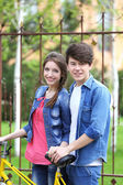 Young couple with bicycle outside — Stock Photo