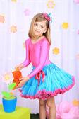 Krásná malá holčička v drobné sukni, zalévání květin na dekorativní pozadí — Stock fotografie