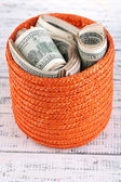 Packs of dollars stored in basket on wooden table — Stock Photo
