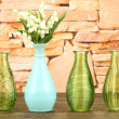 Different decorative vases on shelf on brick wall background — Stock Photo #45452565