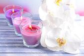 Hermosas coloridas velas y flores orquídeas, sobre tabla de madera de color, en fondo claro — Foto de Stock
