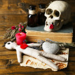 Conceptual photo of love magic. Composition with skull, voodoo doll, dried herbs and candle on  dark wooden background — Stock Photo #45631361