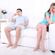Young man and woman  conflict sitting on sofa argue unhappy, on home interior background — Stock Photo #45631597